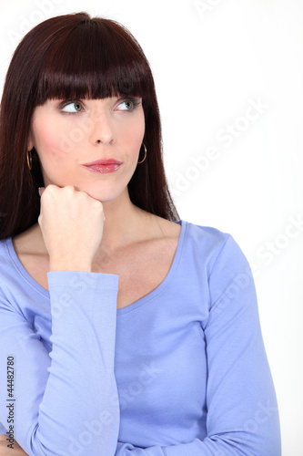 Pensive brunette in white background