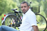 Man sat relaxing next to bicycle