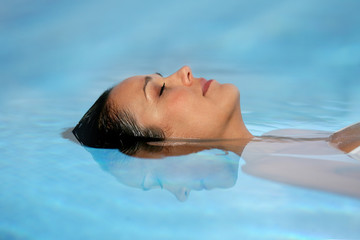 Woman with her eyes closed in a swimming pool