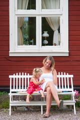 Mutter und Tochter kuscheln auf der Bank vorm Haus