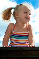 Fröhliches kleines blondes Mädchen mit Zöpfen