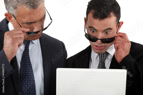 Two businessman taking their sunglasses to look at a laptop.