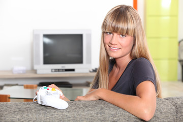 young woman playing video games at home
