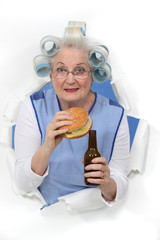 Old woman with beer and a burger