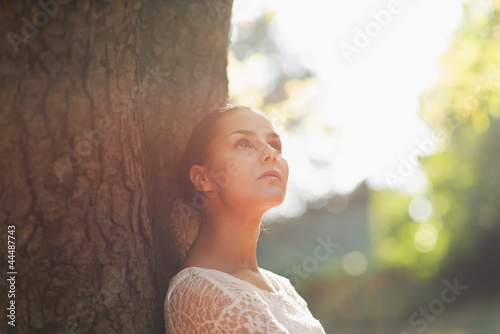 Thoughtful young woman lean against tree