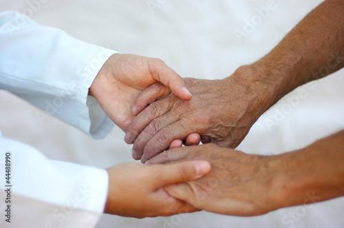 Doctora sosteniendo las manos de un anciano