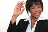 An African American businesswoman gesturing an ok sign.