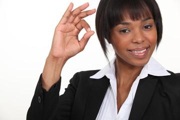 An African American businesswoman gesturing an ok sign.