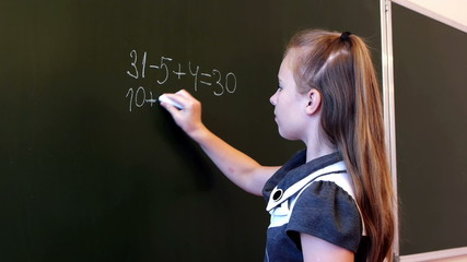 Adorable schoolgirl writing mathematic expression