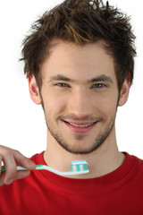 Young man holding a toothbrush