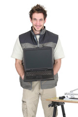 Young tiler holding a laptop with a blank screen