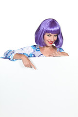 Woman wearing purple wig pointing at advertising board