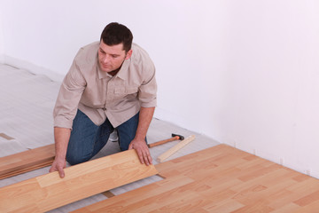 Man laying laminate floor in apartment