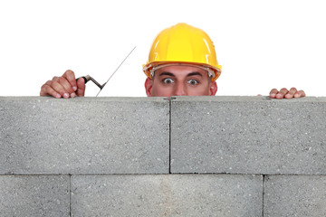 Bricklayer peering over a wall