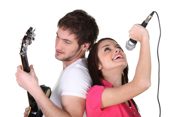 two people singing and playing guitar
