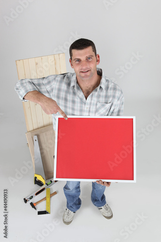 Carpenter pointing to a red poster