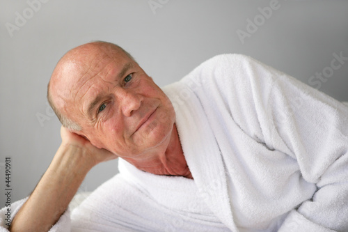 Elderly man lying in his bathrobe