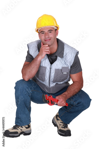 A kneeled plumber.
