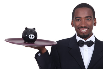 Waiter holding a piggy bank on his tray