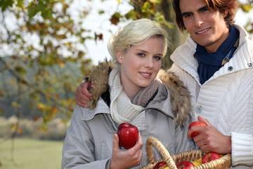 happy couple in the park gathering apples