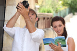 Couple of tourists with camera and guide book