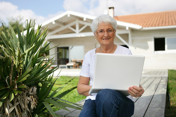 Elderly lady sat outside home with laptop