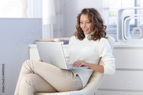 Pretty woman using laptop computer at home