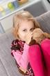 Little girl sucking thumb hugging toy dog