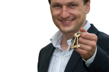 real estate agent holds out the front door key of a new home