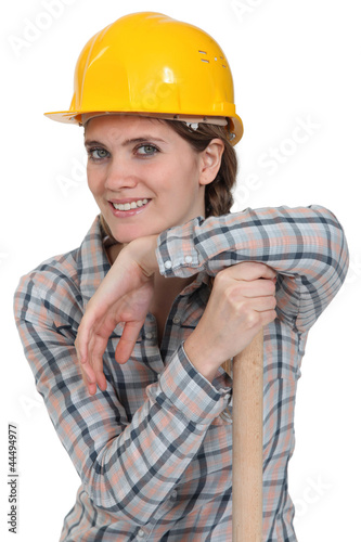 portrait of craftswoman with arm resting on hammer