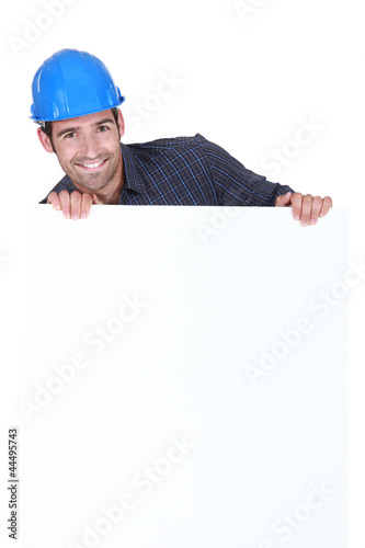 Manual worker stood with advertisement board