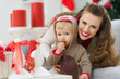 Happy young mother and baby looking on table with Christmas gift