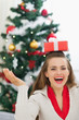 Happy young woman balancing Christmas present box on head