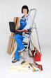 Female carpenter with ladder and laptop