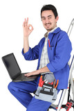 Plumber with laptop and tools on white background