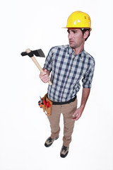 A handyman looking weirdly at his hatchet.