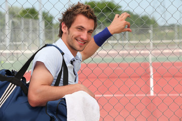 Tennis player leaning against fence