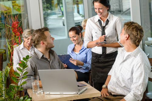 Waitress taking order from businessmen in cafe
