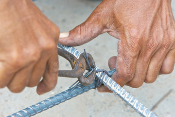 hands of worker use pincers and wires for knitting metal rods