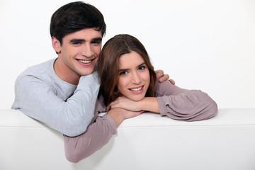 cute young couple sitting in sofa