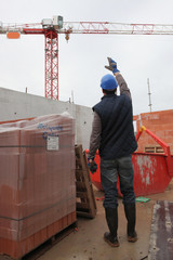 Foreman waving signal to crane operator