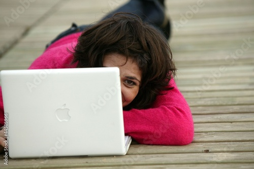 Brunette laying on jetty with computer