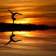 silhouette of female gymnast doing a handstand in sunset