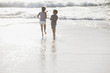 Brother and sister walking on sunny beach
