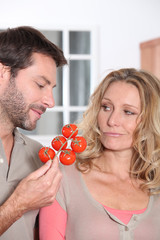 Couple holding tomatoes