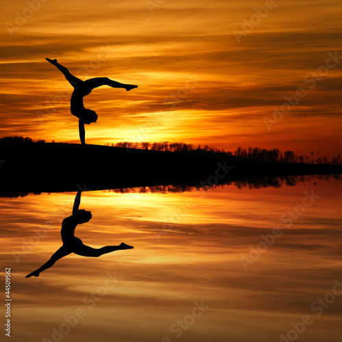 Fototapety, obrazy : silhouette of female gymnast doing a handstand in sunset