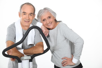 Senior couple using gym equipment
