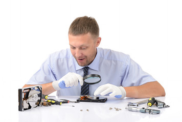 Man wearing gloves repairs hard drive on white background