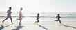 Family running on sunny beach