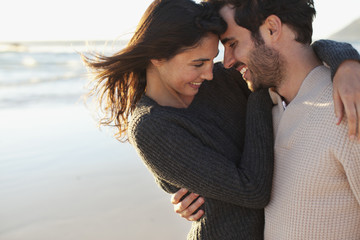 Smiling couple hugging on beach
